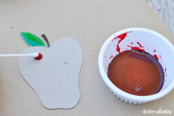 painting cardboard apples with red corn syrup paint