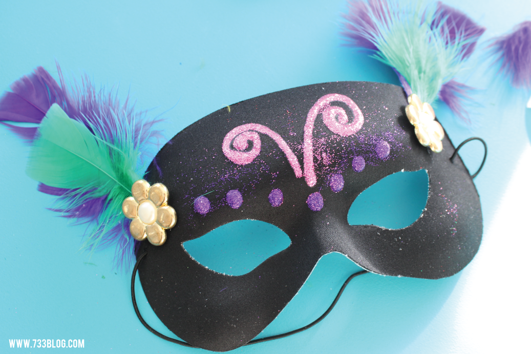 If you plan on using feathers, pick out a few that you like. Glue them onto the mask with hot glue. To cover the stems I also added a large button.  DIY Mardi Gras Mask Kids CraftDIY Mardi Gras Mask Kids Craftmask